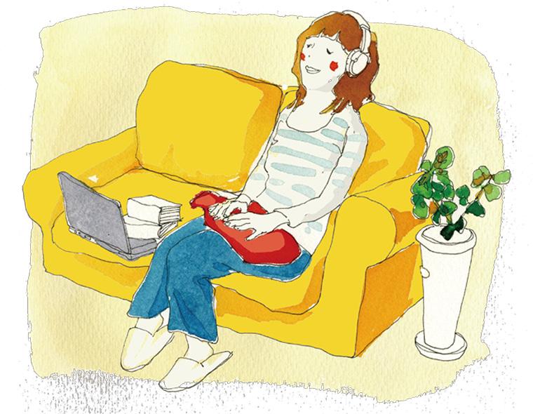 ソファで湯たんぽを膝に置いて、暖まる女性 FASHYの湯たんぽ
