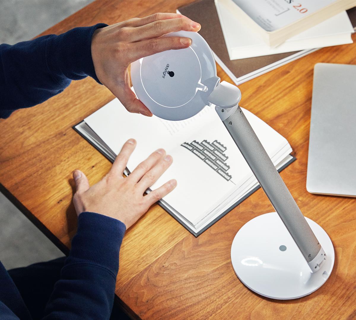 文字がぐっと読みやすく、色もくっきりキレイに。いつも以上に、仕事や勉強、趣味の時間に没頭できる。どんな姿勢でも、ベストポジションを照らしてくれる、手元を大きく・明るく照らすルーペ付き太陽光LEDの「デスクライト」|daylight - Halo Go