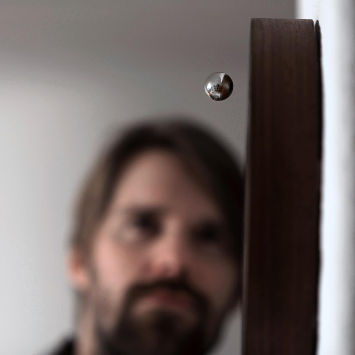 重力に逆らって、クルクルと回転しながら木製ベースの上を周遊するクロム球。あなたの物語を軌道に旅をする時計|Flyte STORY