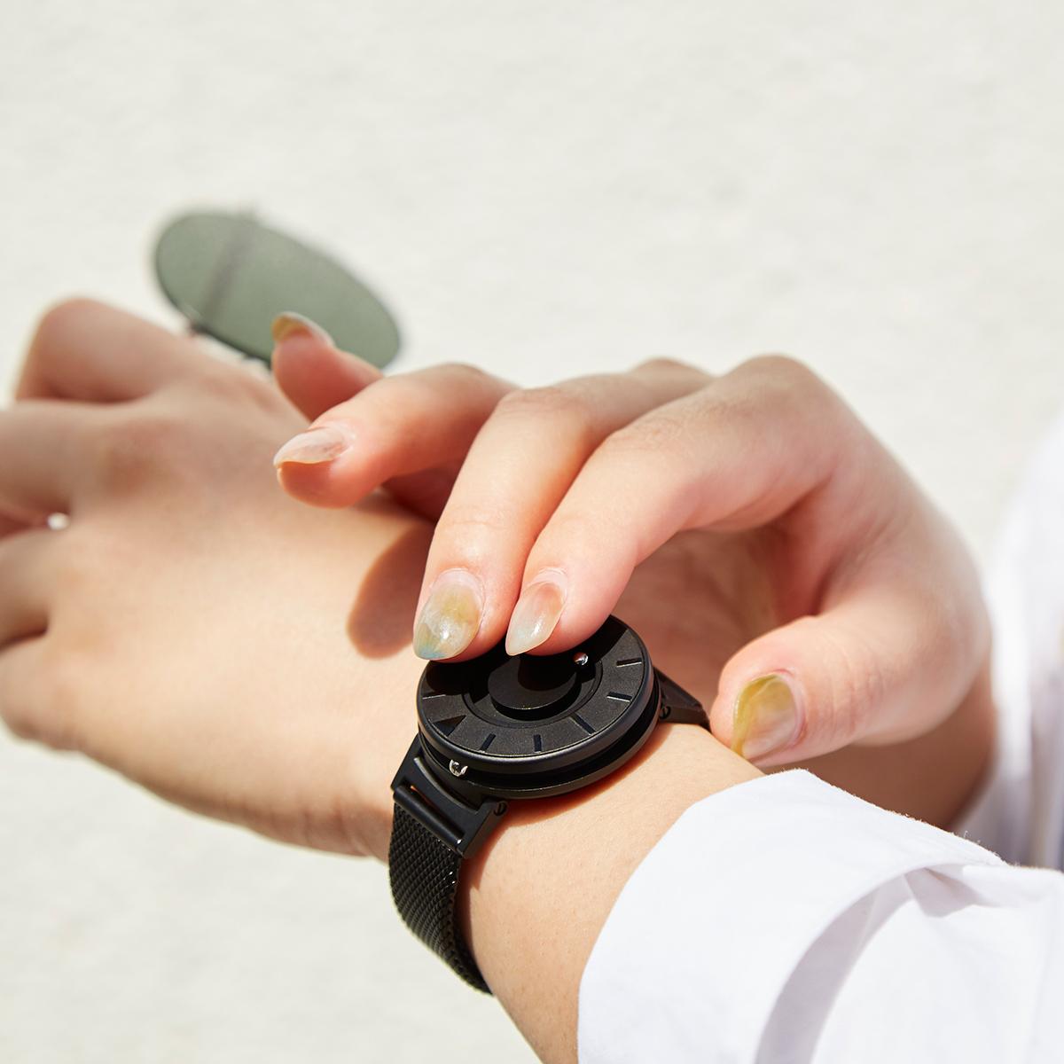 もともと視覚障がい者のために開発されたユニバーサルデザイン時計。腕元におさまるコンパクトな文字盤、軽やかな装着感のメッシュバンド。触って時間を知る「腕時計」| EONE