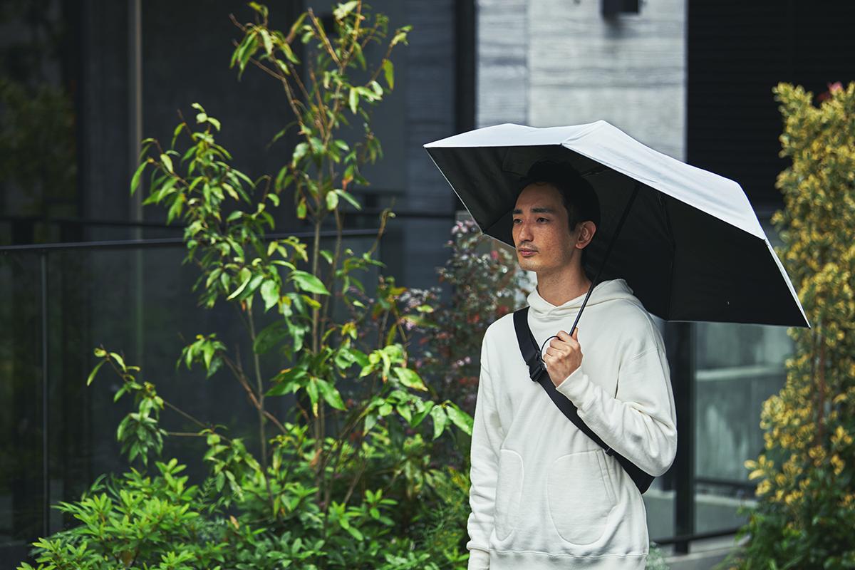 雨の中、バスやタクシー、車へ乗り込むときも、傘をたたむ時間はほんの1秒。驚くほど軽い!完全遮光タイプの「ワンタッチ開閉式折りたたみ傘(晴雨兼用)」|VERYKAL HEAT BLOCK