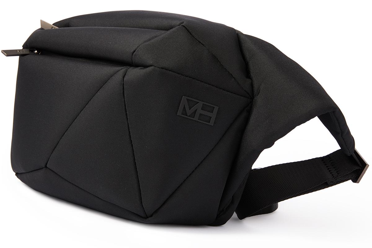 黒一色のミニマルデザイン。いつもの服に背負うだけで、洗練された雰囲気に。「石」から発想したミニマルデザイン、タブレットと上着を入れても型崩れしない「ボディバッグ」|STONE SLING(ストーン スリング)