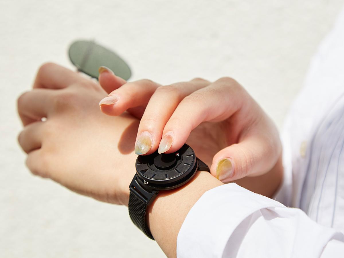 手でそっと触るだけで時間を確認できます。腕元におさまるコンパクトな文字盤、軽やかな装着感のメッシュバンド。触って時間を知る「腕時計」| EONE