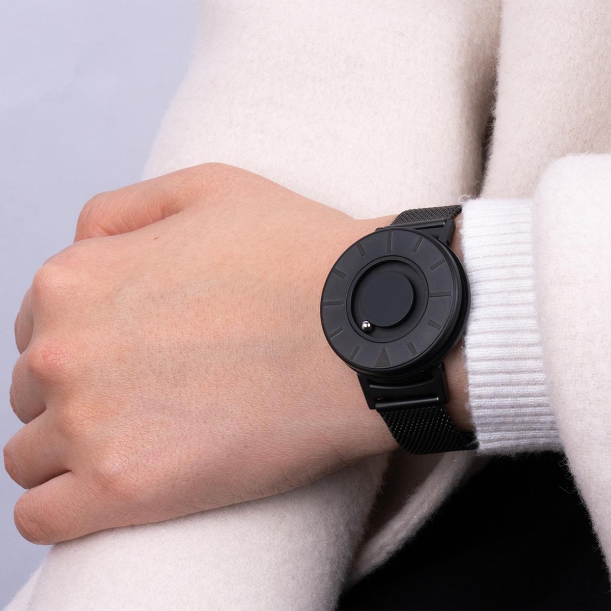 主張していないのにグッと目を引く、重厚感のあるオールブラックは、男女問わず印象的な手元を演出してくれます。腕元におさまるコンパクトな文字盤、軽やかな装着感のメッシュバンド。触って時間を知る「腕時計」| EONE