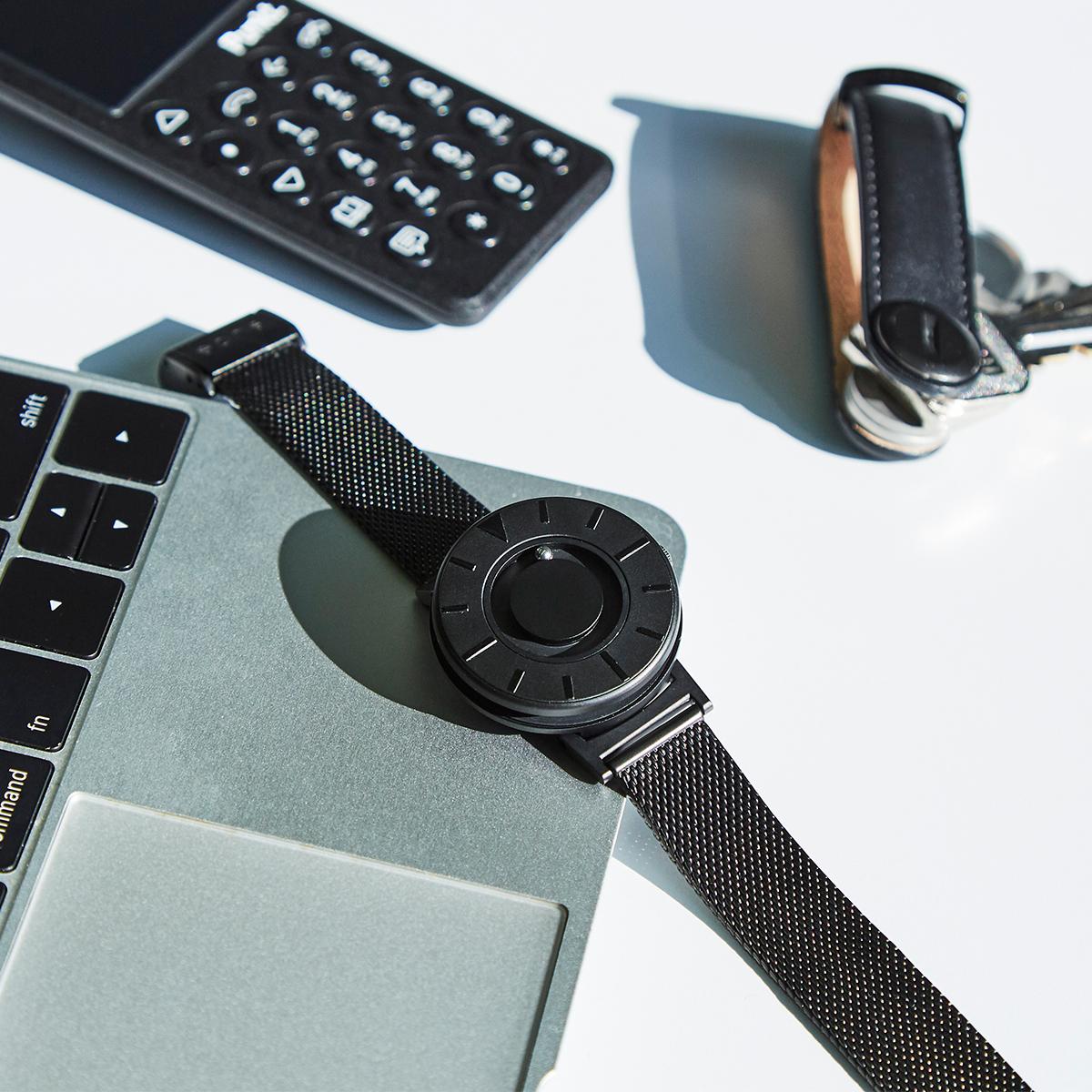 手首が細い方や手が小さめな方にも、バランスよくフィット。腕元におさまるコンパクトな文字盤、軽やかな装着感のメッシュバンド。触って時間を知る「腕時計」| EONE