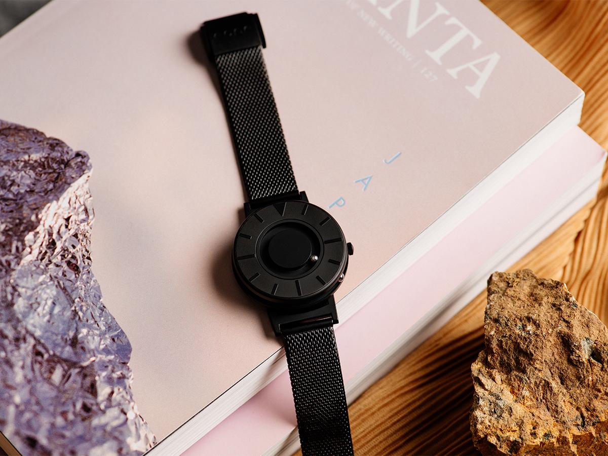 すべての人が楽しめる、ユニバーサルデザイン時計。腕元におさまるコンパクトな文字盤、軽やかな装着感のメッシュバンド。触って時間を知る「腕時計」| EONE