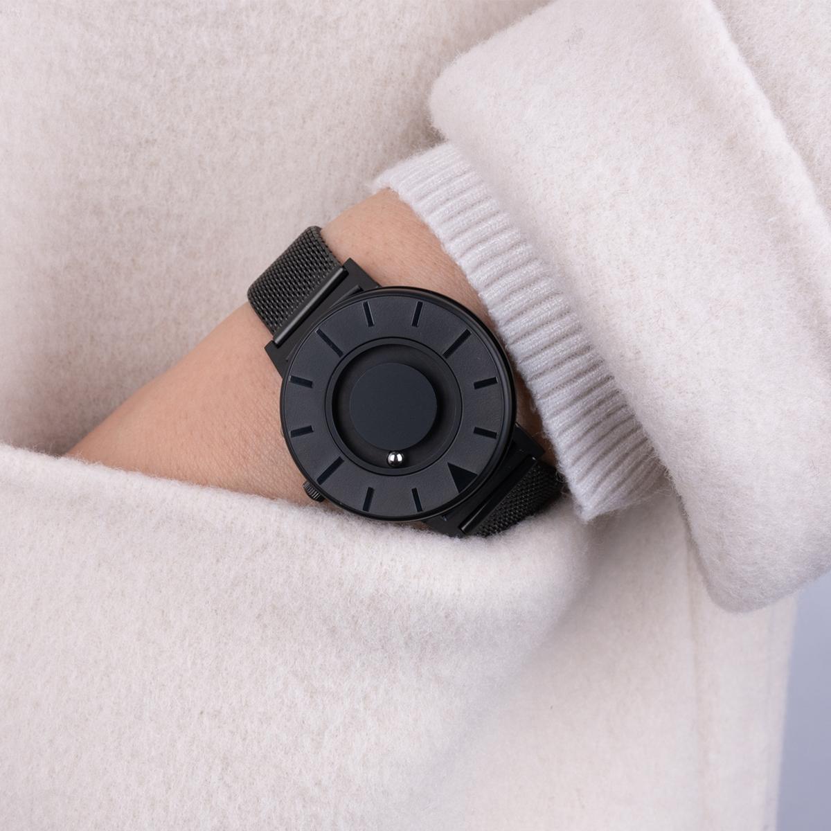 「逆転の発想」が導き出した、美しいユニバーサルデザイン時計の解答。腕元におさまるコンパクトな文字盤、軽やかな装着感のメッシュバンド。触って時間を知る「腕時計」| EONE