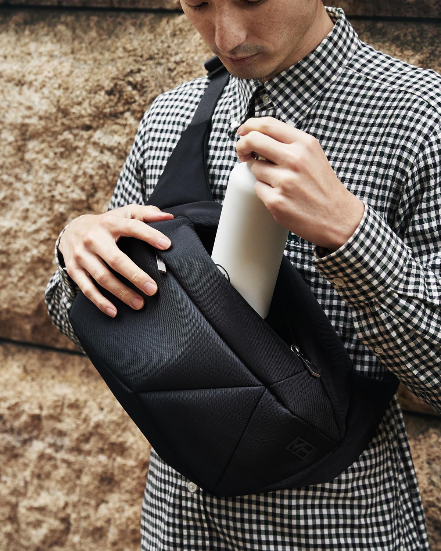 財布やスマホといった必需品はもちろん、上着までスッポリ。タブレットが入るテックポケットもついています。「石」から発想したミニマルデザイン、タブレットと上着を入れても型崩れしない「ボディバッグ」|STONE SLING(ストーン スリング)