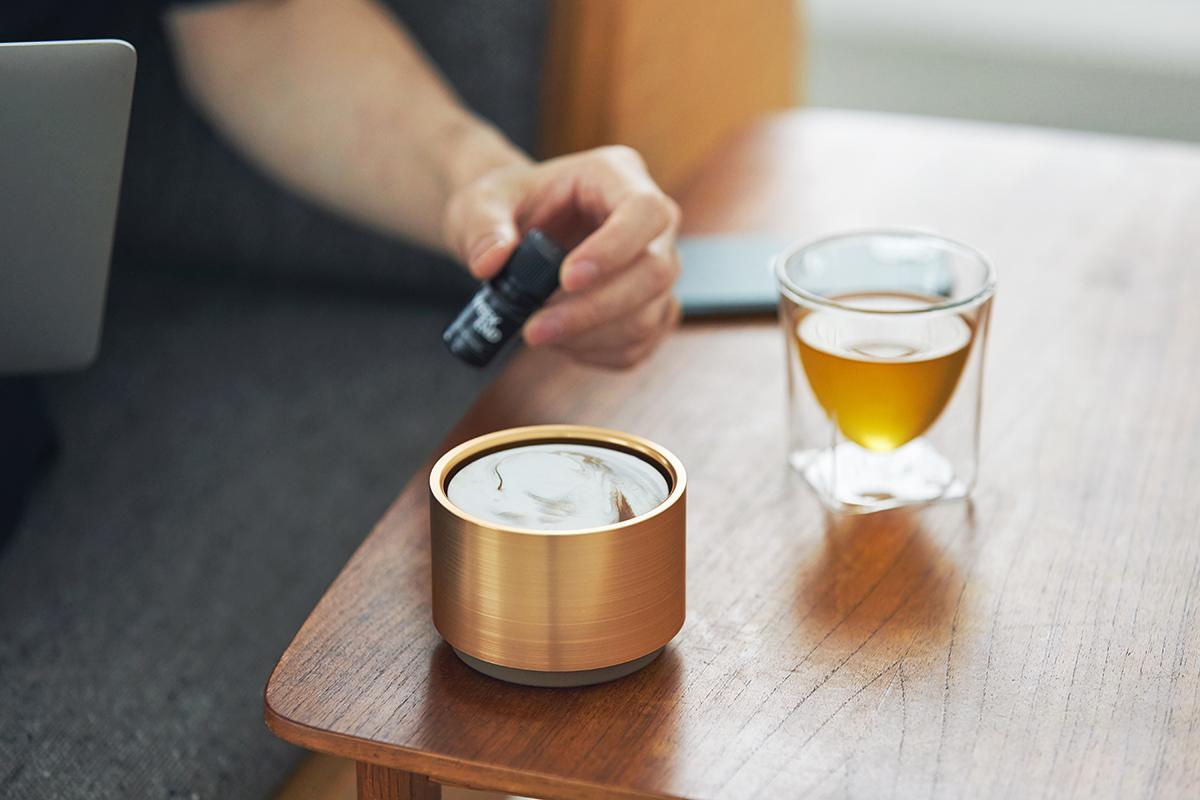 ゴールドは、ヘアライン加工(単一方向に細かい傷をつける)を施し、金属的な質感を。木のテーブルとの相性も抜群。|ミニマムでおしゃれなデザイン家電。香炉のような静かな存在感の「アロマディフューザー」|WEEKEND(ウィークエンド)