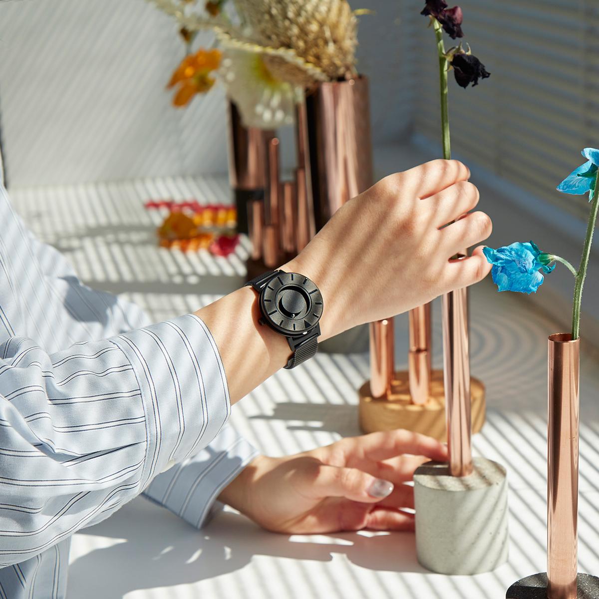 華奢な女性の腕元にも品よくフィット。もちろん、男性やお子さまにもおすすめしたい、ひとまわり小さなモデル。腕元におさまるコンパクトな文字盤、軽やかな装着感のメッシュバンド。触って時間を知る「腕時計」| EONE